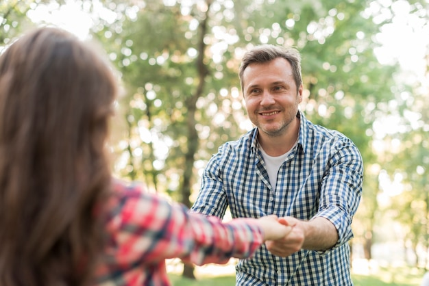 Uomo felice che tira sua figlia e giocando al parco Foto Gratuite