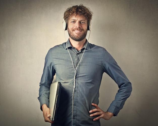 Uomo felice con cuffie e laptop Foto Premium