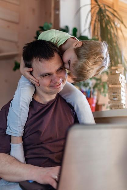 Uomo felice con i bambini che utilizzano computer portatile e trasduttore auricolare durante il suo lavoro domestico, vita nella quarantena Foto Premium