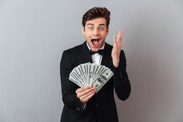 Uomo felice di grido in vestito ufficiale che tiene soldi. Foto Gratuite