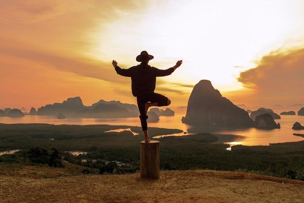 Uomo felice in vestiti neri che fanno posa di yoga che sta sull'albero Foto Premium