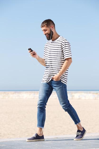 Uomo felice integrale in cuffie che cammina sulla spiaggia con il ... 4e41c6a1c7a8