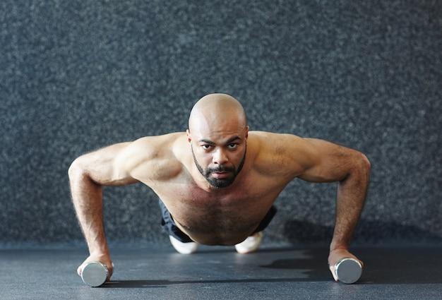 Uomo forte che spinge verso l'alto sui manubri con sforzo Foto Gratuite