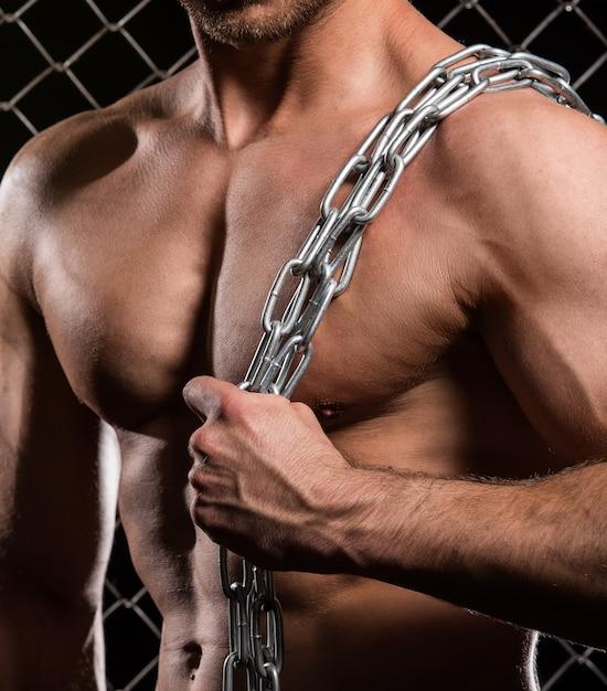 Uomo forte sul recinto con catene Foto Gratuite