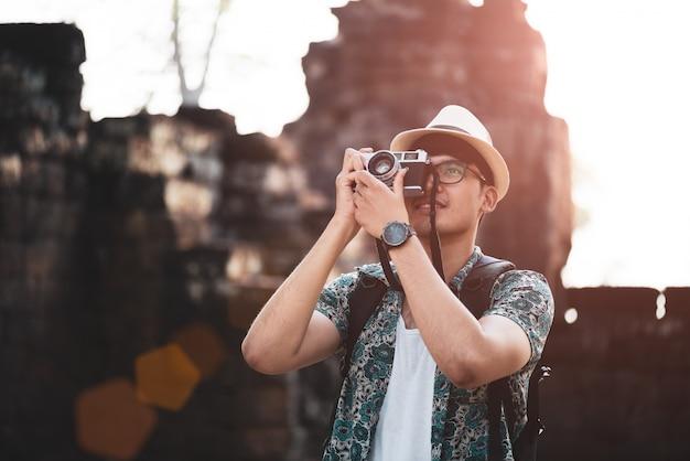 Uomo fotografo viaggiatore con zaino a scattare foto con la sua macchina da presa retrò Foto Premium