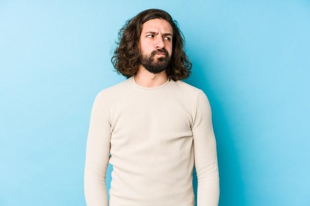 Uomo giovane capelli lunghi su una parete blu confuso, si sente dubbioso e incerto. Foto Premium