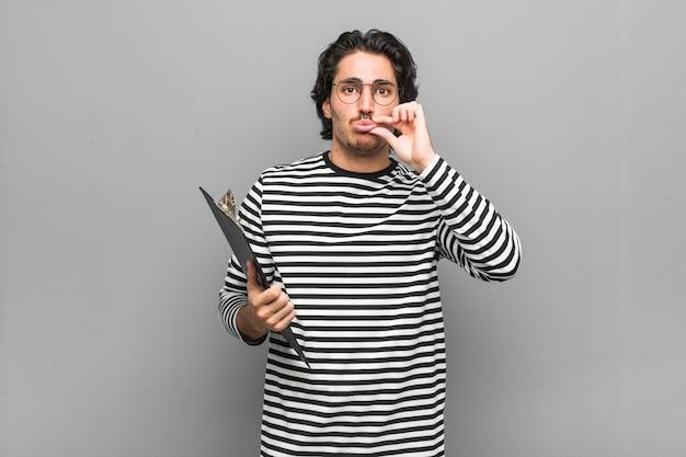 Uomo giovane impiegato in possesso di un inventario con le dita sulle labbra mantenendo un segreto. Foto Premium