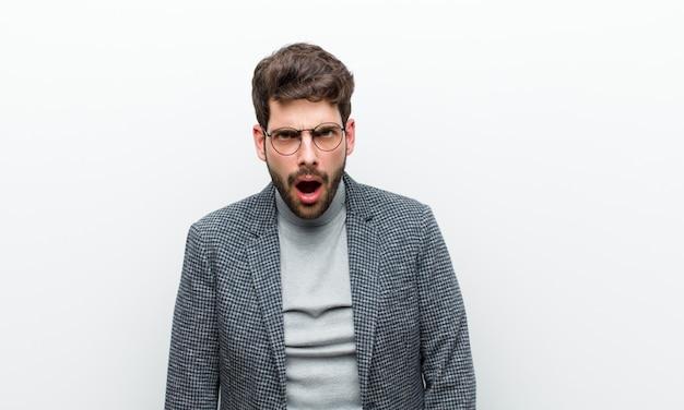 Uomo giovane manager dall'aspetto scioccato, arrabbiato, seccato o deluso, a bocca aperta e furioso Foto Premium