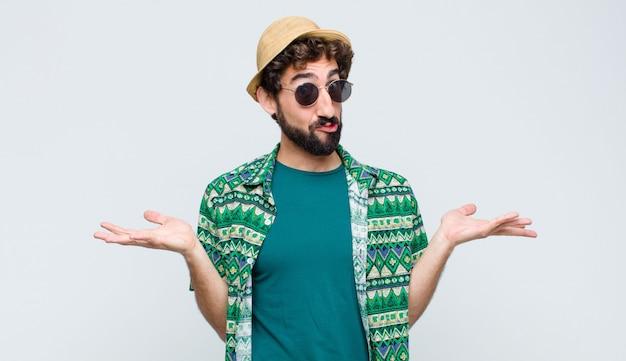 Uomo giovane turista sentirsi perplesso e confuso, dubitando, ponderando o scegliendo diverse opzioni con espressione divertente sul muro bianco Foto Premium
