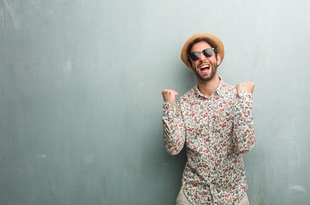 Uomo giovane viaggiatore che indossa una maglietta colorata molto felice ed emozionato, alzando le braccia Foto Premium