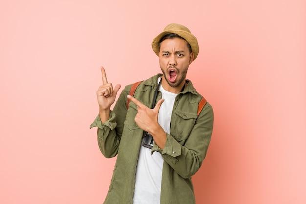 Uomo giovane viaggiatore filippino che punta con gli indici verso uno spazio di copia, esprimendo eccitazione e desiderio Foto Premium