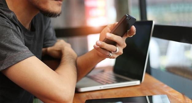 Uomo in abbigliamento casual con smartphone mobile in mano e computer portatile sul tavolo Foto Premium