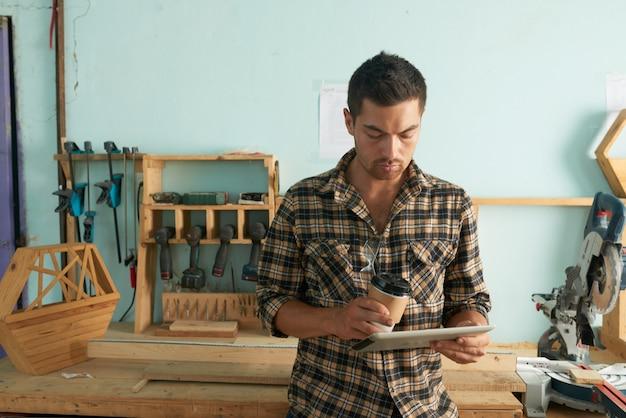 Uomo in abbigliamento casual controllando le e-mail con la lavorazione del legno in background Foto Gratuite