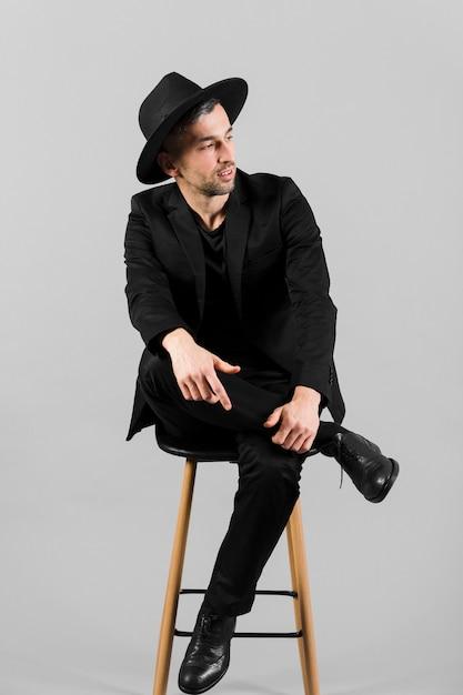 Uomo in abito nero, guardando lontano e seduto su una sedia Foto Gratuite