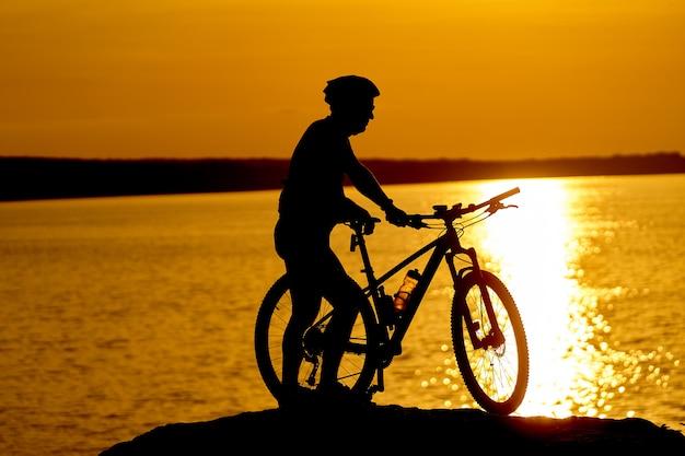 Uomo in bicicletta in spiaggia sulla stagione estiva crepuscolare Foto Premium