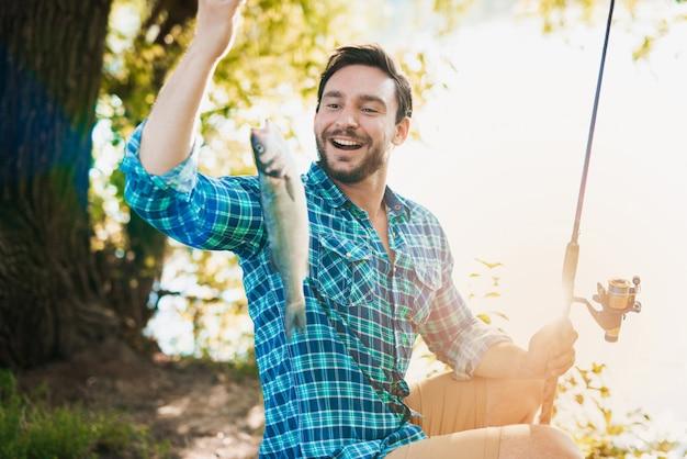 Uomo in camicia a scacchi pesca sul fiume in estate. Foto Premium