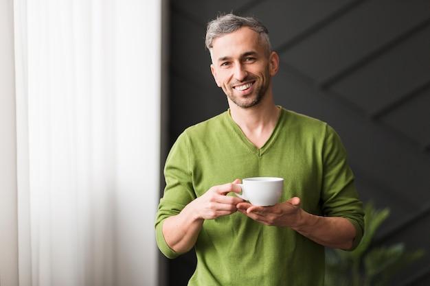 Uomo in camicia verde che tiene una tazza di caffè bianca e sorrisi Foto Gratuite