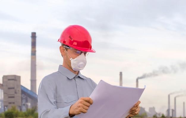 Uomo in casco sullo sfondo della pianta Foto Premium