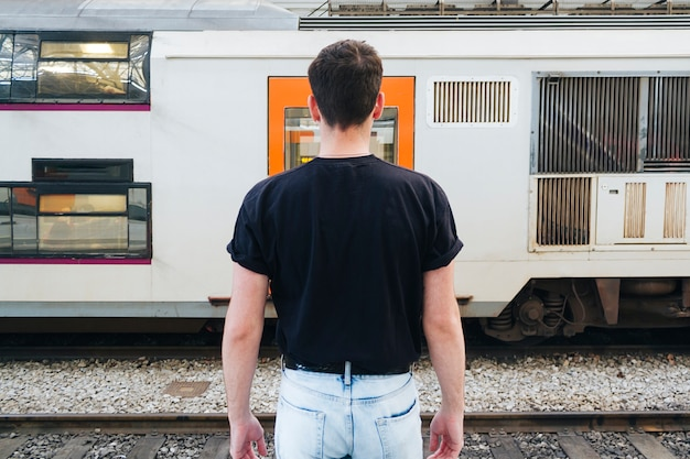 Uomo in maglietta nera che sta davanti al treno ferroviario Foto Gratuite