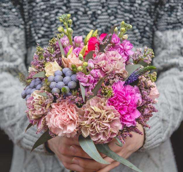 Uomo in maglione di lana che tiene un mazzo di fiori misti Foto Gratuite