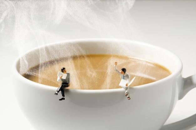 Uomo in miniatura di affari che si siede sul bordo bianco caldo della tazza di caffè del vapore Foto Premium