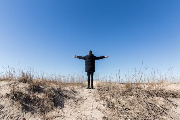 Uomo in nero che resta sulla collina su sfondo blu cielo Foto Premium