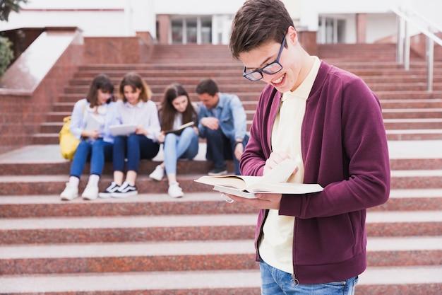 Uomo in occhiali in piedi e leggendo il libro nelle mani Foto Gratuite