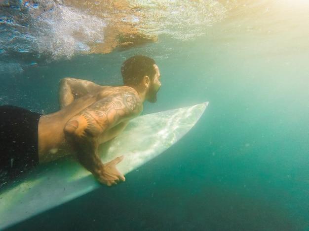 Uomo in pantaloncini immersioni con tavola da surf sott'acqua Foto Gratuite