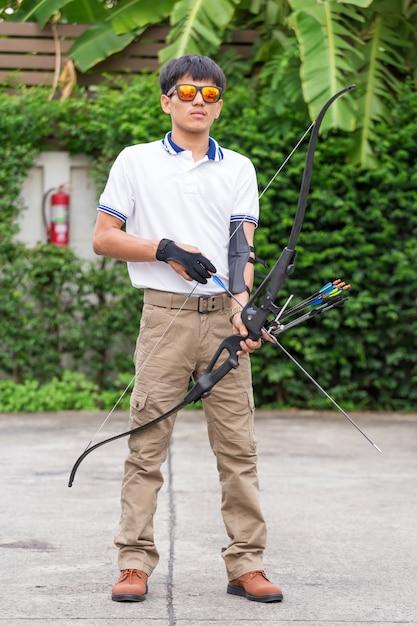 Uomo in pantaloni cargo con arco e frecce Foto Premium