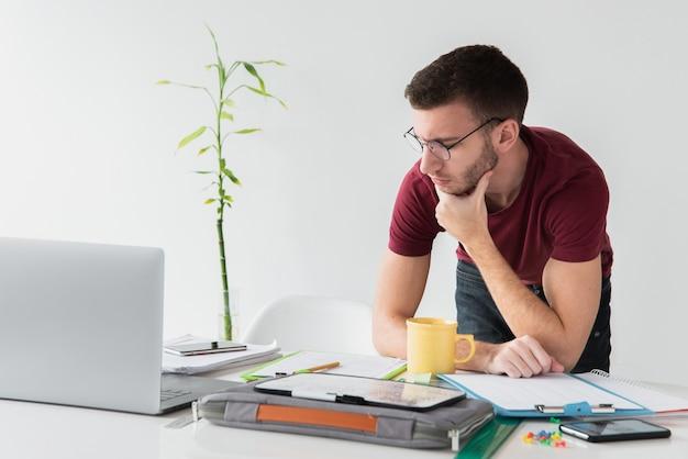 Uomo in piedi alla sua scrivania e guardando lontano Foto Gratuite