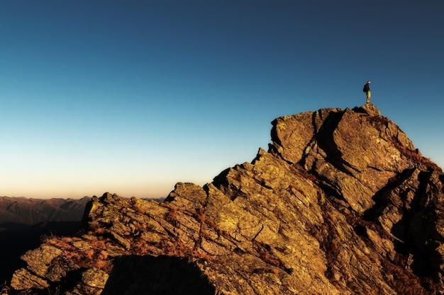 Uomo in piedi sulla cima della roccia durante il giorno Foto Gratuite