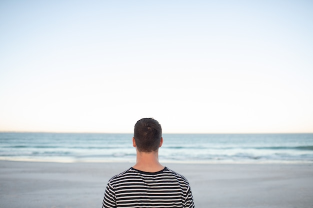 Uomo in piedi sulla spiaggia Foto Gratuite