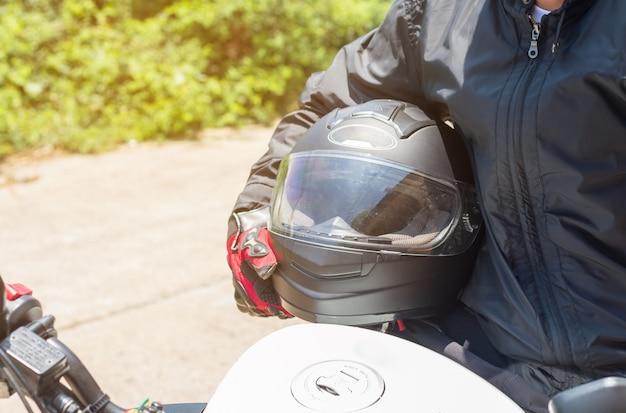 Uomo in una moto con casco e guanti indumenti protettivi per il motociclismo Foto Premium