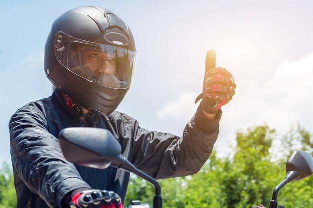Uomo in una moto con casco e guanti per il controllo dell'acceleratore del motociclismo con la luce del sole Foto Premium