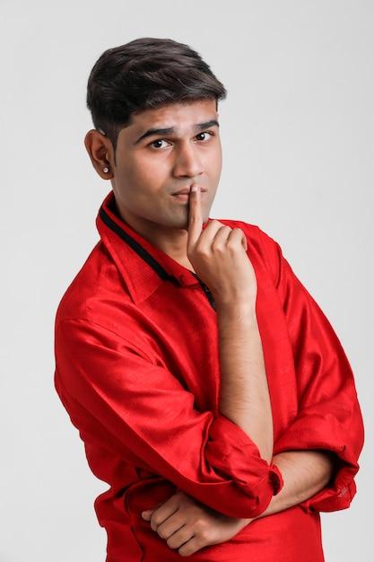 Uomo indiano / asiatico in camicia rossa e mostrando espressione multipla sopra bianco Foto Premium