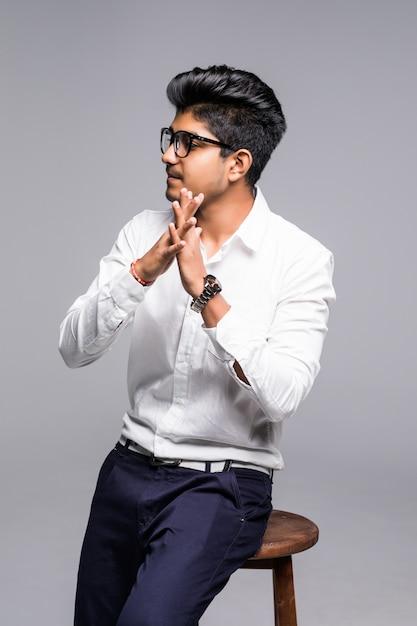 Uomo indiano bello bello che si siede su una sedia e che si rilassa, isolato per la parete bianca Foto Gratuite