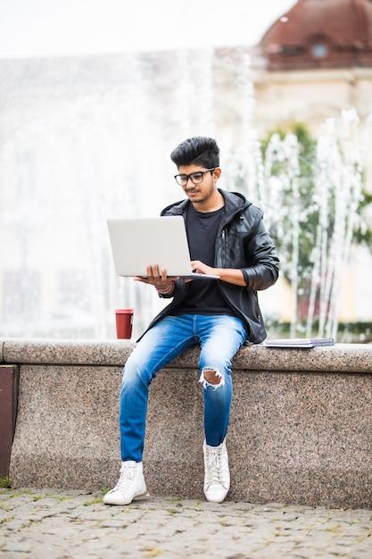 Uomo indiano bello con il computer portatile mentre sedendosi vicino alla fontana nel centro urbano un giorno Foto Gratuite