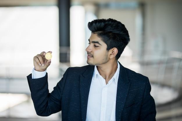Uomo indiano di affari in vestito con bitcoin dorato in ufficio moderno Foto Gratuite