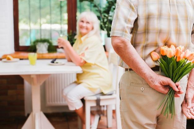 Uomo invecchiato del raccolto che prepara mazzo per il coniuge Foto Gratuite