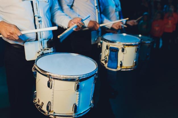 Uomo irriconoscibile che marcia mentre suona il tamburo sul tamburo. Foto Premium