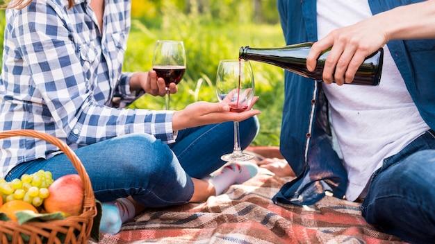 Uomo irriconoscibile che versa vino negli occhiali durante la data Foto Gratuite