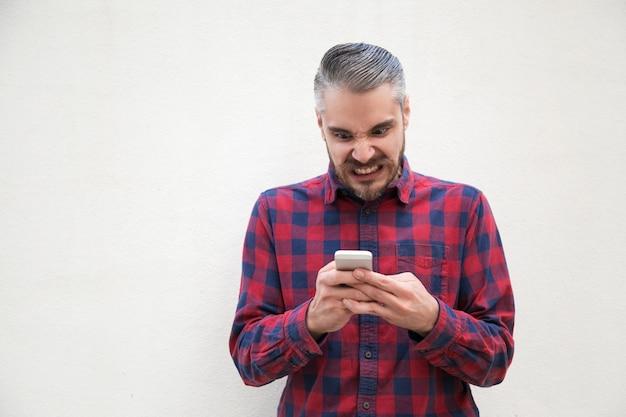 Uomo irritato che per mezzo del telefono cellulare Foto Gratuite