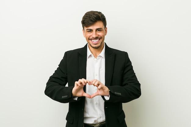 Uomo ispanico di giovani affari che sorride e che mostra una forma del cuore con le mani. Foto Premium