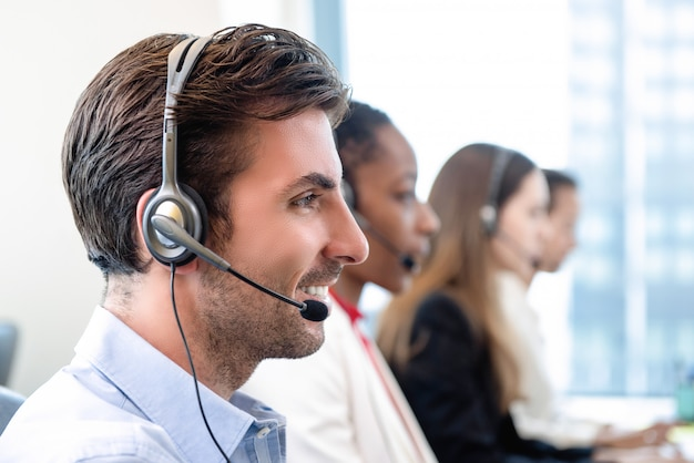 Uomo ispanico in ufficio call center con la squadra Foto Premium