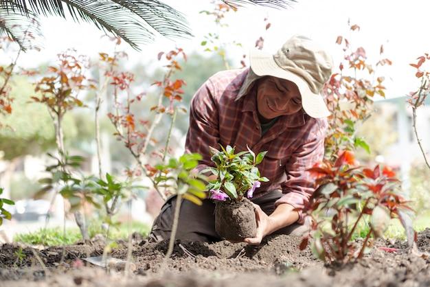 Uomo latino che pianta i fiori in un bello giardino verde Foto Premium