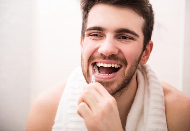 Uomo lavarsi i denti e guardarsi allo specchio. Foto Premium