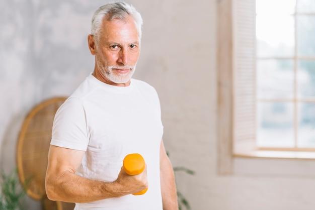 Uomo maggiore anziano che alza i pesi durante la sessione di allenamento della palestra Foto Gratuite
