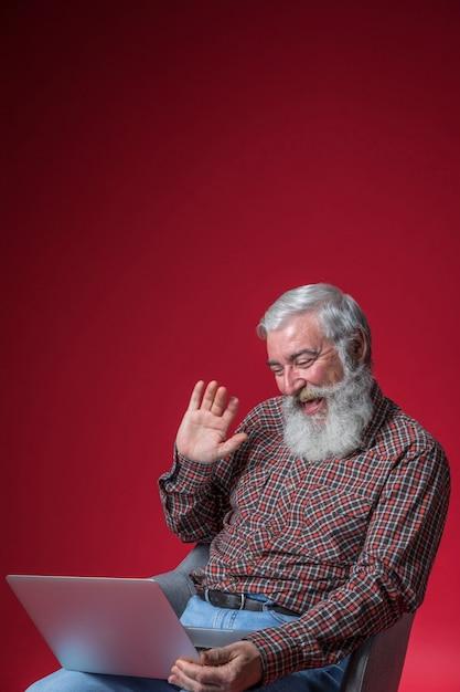 Uomo maggiore felice che fluttua la loro mano mentre video che chiacchiera sul computer portatile contro il contesto rosso Foto Gratuite