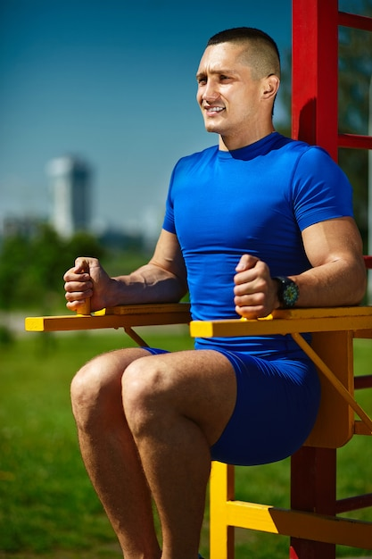 Uomo maschio dell'atleta felice sano sano bello che si esercita al parco della città - concetti di forma fisica un bello giorno di estate sulla barra orizzontale Foto Gratuite