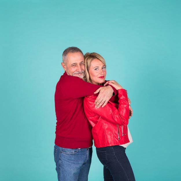 Uomo maturo che abbraccia sua moglie da dietro su sfondo turchese Foto Gratuite